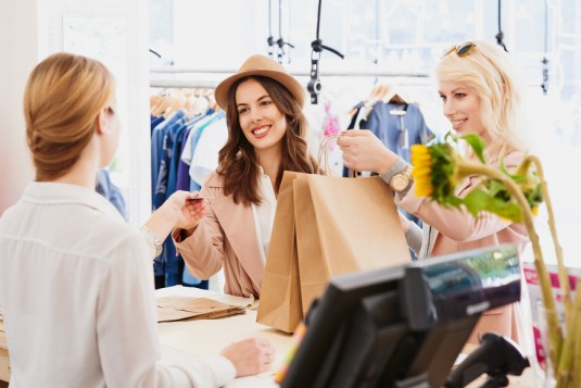 Friends Shopping with credit card in fashion boutique